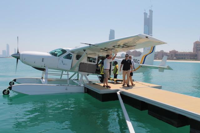 Kleines Wasserflugzeug am Landungssteg im kristallblauen Wasser mit Passgieren